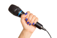 Woman's hand holding a microphone. Woman's hand with blue fingernails holding a black microphone royalty free stock images