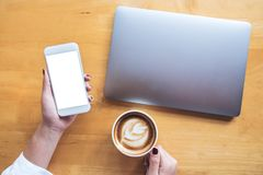 Top view mockup image of a woman`s hand holding mobile phone with blank white desktop screen while using laptop with coffee cup Royalty Free Stock Photography