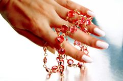Woman's hand holding a necklace Stock Images