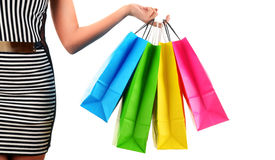 Woman's hand holding paper shopping bags isolated on white Stock Photos