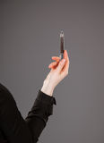 Woman's hand holding a pen. On grey background Royalty Free Stock Photos