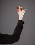 Woman's hand holding a pen. On grey background Stock Photos