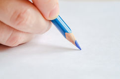 Woman`s hand holding a pencil on white. Woman`s hand holding blue pencil against the white background. Drawing action Royalty Free Stock Photography