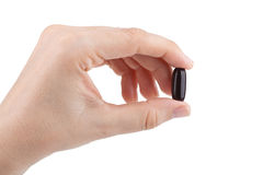 Woman's hand holding a pill Royalty Free Stock Photos