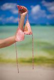 Woman's hand holding pink bra background the sea Stock Photo