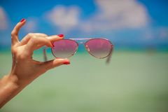 Woman's hand holding pink sunglasses on tropical Royalty Free Stock Photo