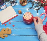 Woman`s hand holding a red ceramic mug with hot chocolate and ma. Rshmallow over a blue wooden table, new year background stock photo