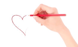 Woman's hand holding a red pencil and drawing a heart Royalty Free Stock Photography
