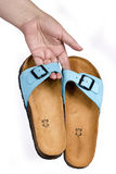 Woman's hand holding a sandals. Woman's hand holding a blue sandals Royalty Free Stock Photos