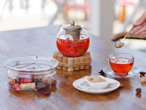 A composition of a teapot full of organic ceylon and berries tea on a wooden table and on an outdoors background. A woman`s hand is holding a silver spoon with Stock Photography