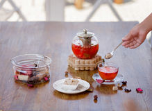 A composition of a teapot full of organic ceylon and berries tea on a wooden table and on an outdoors background. A woman`s hand is holding a silver spoon with Royalty Free Stock Photography