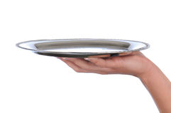 Woman's hand holding a silver tray. Closeup of a woman's hand holding up a silver serving tray over a white background royalty free stock photography