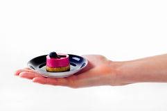Woman`s hand holding small dessert cake on delicate set plate Stock Photo