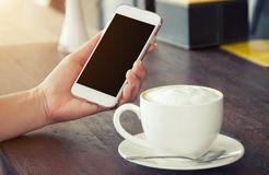 Woman`s hand holding a smart phone. And a cup of hot coffee on the table Royalty Free Stock Photo