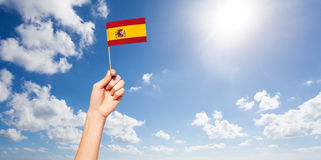 Woman`s hand holding Spanish flag against blue sky Royalty Free Stock Photos