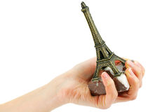 Woman's hand holding statuette of Eiffel Tower. Isolated on a white background Stock Images