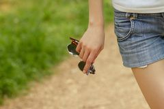 Woman's hand holding sunglasses Royalty Free Stock Image