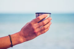 Woman's hand holding a thermos cup by the sea Stock Photo