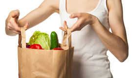 Woman's hand holding vegetables and fruits in shopping bag Stock Photo