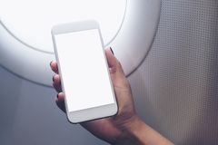 Woman`s hand holding a white smart phone with blank desktop screen next to an airplane. Mockup image of woman`s hand holding a white smart phone with blank Stock Photography