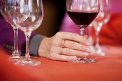 Woman's Hand Holding Wine Glass At Restaurant Table Stock Photos