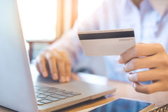 A woman`s hand holds a credit card and uses a laptop to shop onl Royalty Free Stock Photography