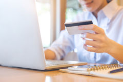 A woman`s hand holds a credit card and uses a laptop to shop onl Royalty Free Stock Photo