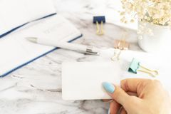 Woman& x27;s hand holds an empty business card in the office on marble table. Woman& x27;s hand holds an empty business card in the office, in the background is royalty free stock photography