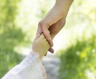A woman`s hand holds a small child`s hand, close-up, nature royalty free stock photo