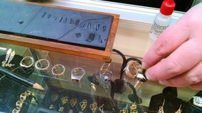 Metallurgist performs acid tests on jewelry to be traded. A woman`s hand holds a sterling silver ring placed in alignment with other earrings and metals for stock photo
