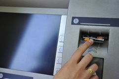 Woman's hand inserting card into cash dispense stock photography