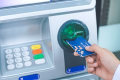 Woman`s hand inserting debit card into an ATM. Machine stock photos