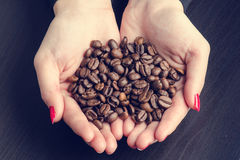Woman´s hand keep coffee beans on a dark background. Stock Photography