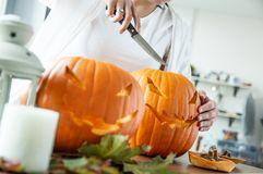Woman`s hand with knife cuts pumpkin for Halloween royalty free stock image