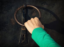 Woman's hand knocking on the door with knocker. Woman's hand knocking on the old door with knocker royalty free stock photos