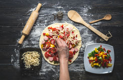 Woman`s hand lays out the ingredients on the pizza Stock Photo