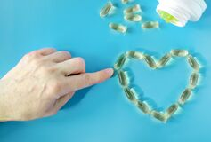 A woman`s hand lays out the symbolic outline of a heart from capsules with fish oil