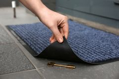 Woman`s hand lifting door mat to reveal key hidden underneath. Closeup stock image