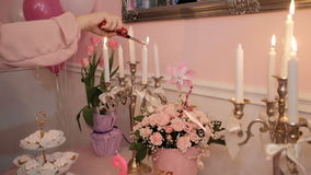 Woman`s hand lights wax candles on table in living room. In banquet hall number handsome skied ball have beautifully arranged bouquets of pink roses and tulips stock footage