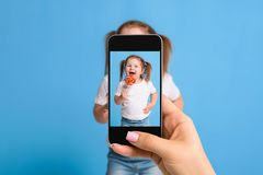 Woman`s hand making photo of a little girl with a mobile phone. Selective focus on a mobile phone with a portrait of a Royalty Free Stock Photos