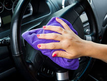 Woman's hand with microfiber cloth polishing wheel of a car Royalty Free Stock Photo