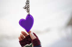 Woman's hand in mittens reaching for a heart Royalty Free Stock Image