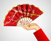 Woman`s hand with open chinese red fan isolated on white Stock Image
