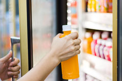 Woman`s hand open convenience store refrigerator shelves and pic. K product Stock Photos