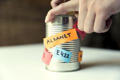 Woman`s hand opening canned food with paper notes naming food additives. Healthy food concept.  stock images
