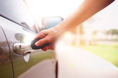 Woman`s hand opening a car`s door with key Stock Photo