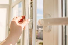 Woman`s hand opening pvc window on the background of high-rise b royalty free stock image