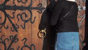 A woman s hand opens the door, a close-up photo. The hand holds onto the antique metal handle. he doorman opens. A woman s hand opens the door, a close-up photo stock footage