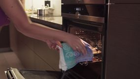 Woman`s hand opens oven, takes burnt cookies, smoke from overcooked food coming