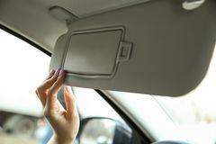 Woman`s hand opens the sun visor in the car. stock image